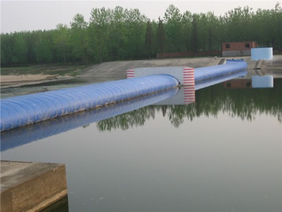 A blue water inflatable rubber dam is under the pier and water level is low.