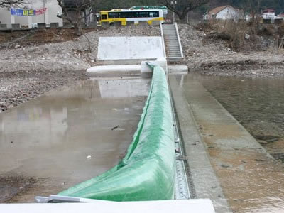A green bookend rubber dam is in the river which water level is low.
