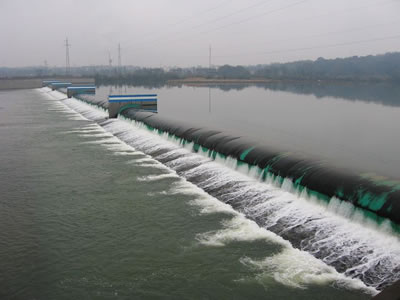 A green water inflatable rubber dam with black protective layer has overflow and many piers.