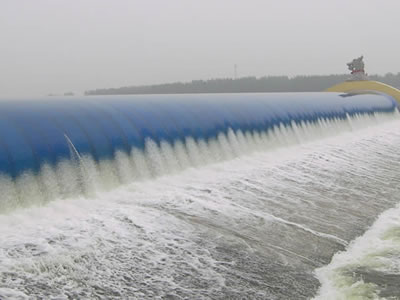 Blue water inflatable rubber dam has overflow and many piers.