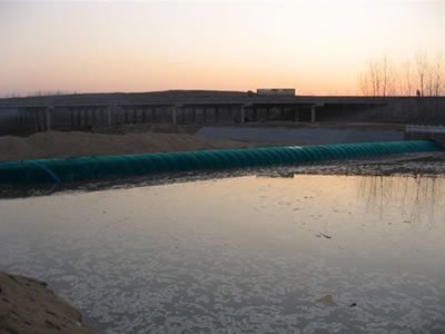 A blue water inflatable rubber dam retain water in one side.